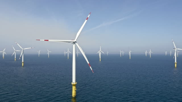 aerial wind farm at sea in sunshine - environmental conservation stock videos & royalty-free footage
