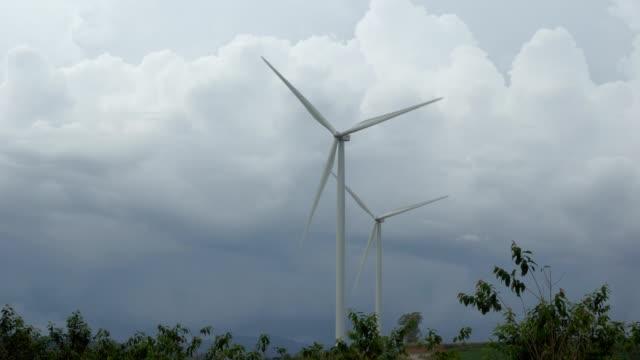 vídeos de stock e filmes b-roll de a wind farm of wind turbines creating green energy on little hill - moinho