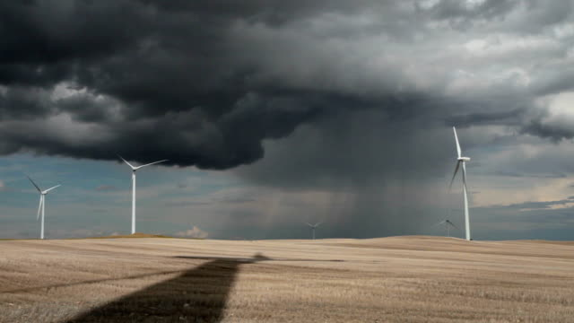 POV of wind farm tower shadow on wheat stubble field with dramatic clouds.