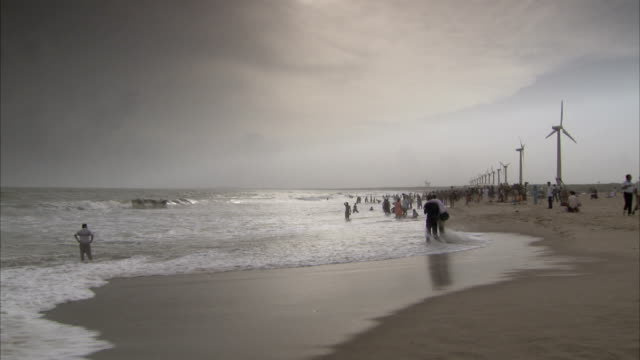 Wind farms line Mandvi beach where vacationers relax and enjoy themselves. Available in HD.