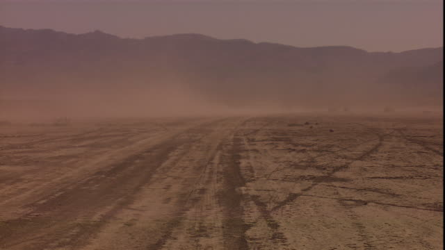 wind kicks up dust in a barren desert. - nevada stock videos & royalty-free footage