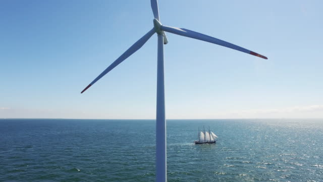Wind power showed by wind turbine and sail boat