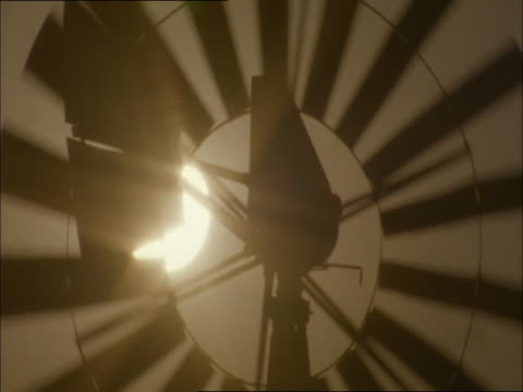 a wind pump spins in front of a golden-hour sun. - golden hour stock videos & royalty-free footage