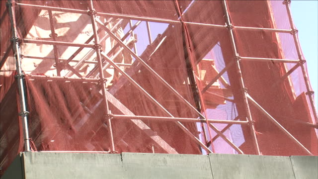 wind ripples a fabric wrap that encloses a construction site. - 足場点の映像素材/bロール