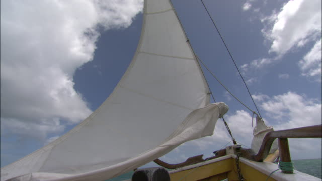 wind rustles a sail as it is raised in a sailboat. - sail stock videos & royalty-free footage