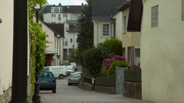 wind rustles foliage on garden walls in narrow alley with parked cars as van drives by - frankfurt, germany - narrow stock videos & royalty-free footage