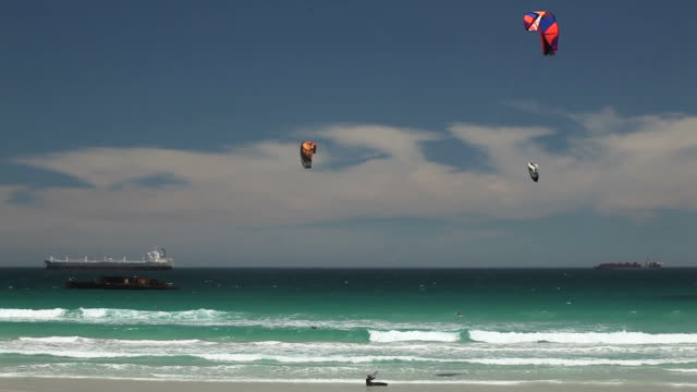 wind surfers in the sea at bloubergstrand in cape town - kiteboarding stock videos & royalty-free footage