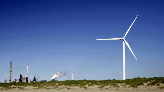 stockvideo's en b-roll-footage met wind turbine and steel factory - noord holland