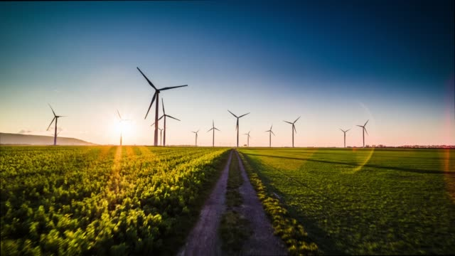 antenne: turbine windpark bei sonnenuntergang - feld stock-videos und b-roll-filmmaterial