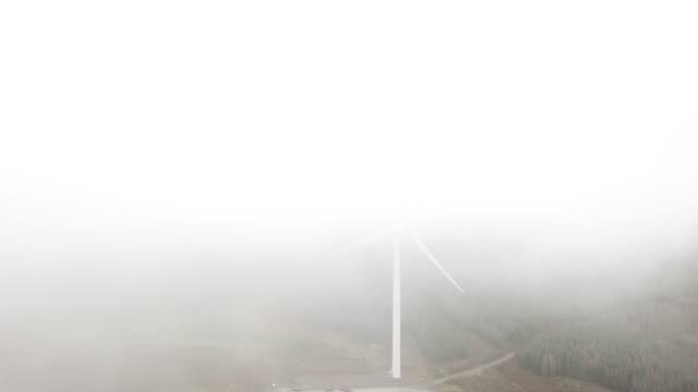a wind turbine in a forest covered in cloud - energy efficient stock videos & royalty-free footage