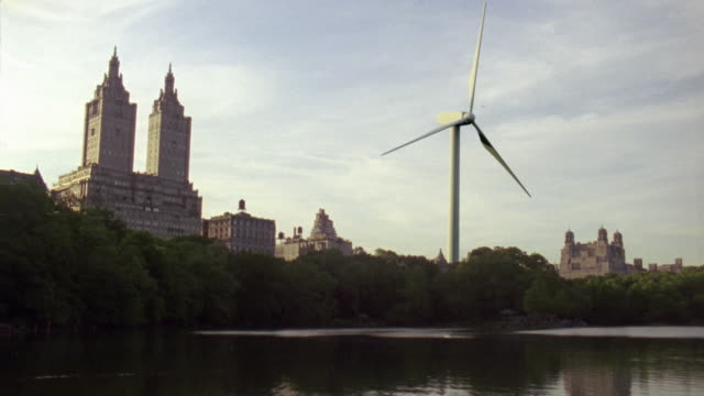 vídeos de stock, filmes e b-roll de ws wind turbine in central park seen across pond / new york city, new york, usa - 2009