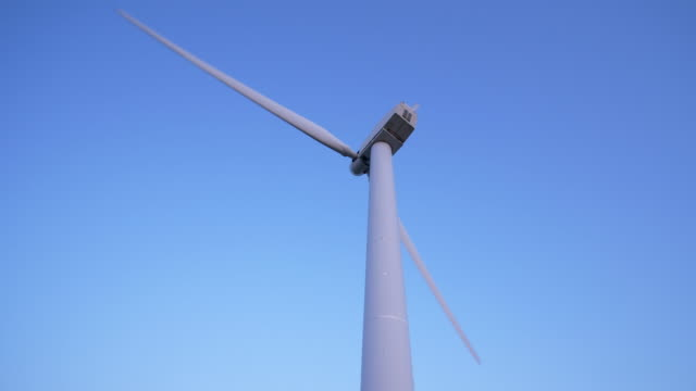 wind turbine on a hill (tilt up) - 発電所点の映像素材/bロール