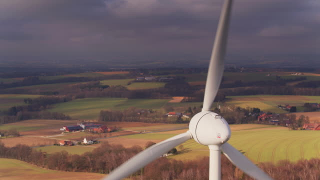 vídeos de stock e filmes b-roll de wind turbine overlooking farmland in north rhine-westphalia - drone shot - gerador
