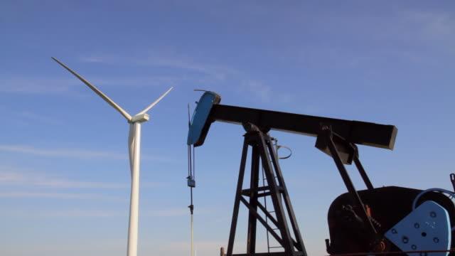 vídeos de stock e filmes b-roll de turbina eólica, céu, plataforma petrolífera - combustível fóssil