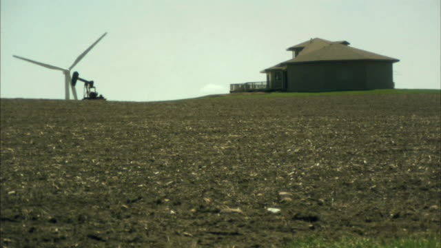 vídeos de stock, filmes e b-roll de ws wind turbine spinning next to oil pump and house in field/ buffalo ridge, minnesota - grupo pequeno de objetos