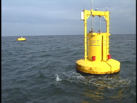 wind turbine stands on a ship deck in the east river; energy buoys float in the ocean. - buoy stock videos & royalty-free footage
