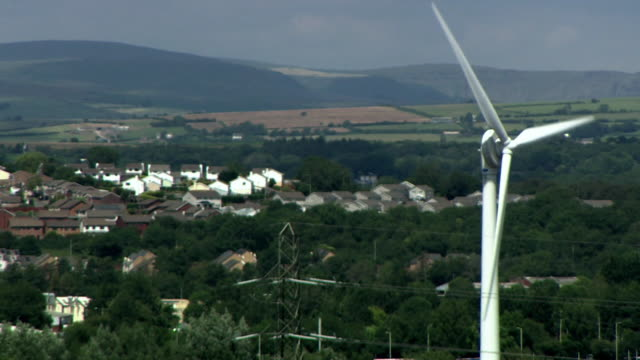 wind turbine with electricity pylon and housing estate in the background cornwall - built structure stock videos & royalty-free footage