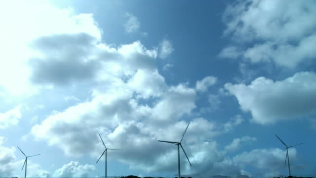 T/L Wind turbines against sky with clouds