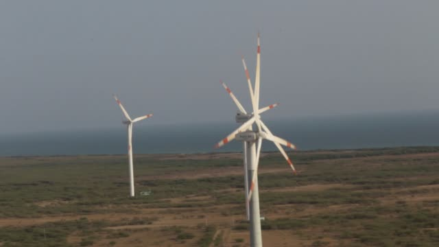 Wind turbines and electricity pylons stand at the Suzlon Energy Ltd Nani Sindhodi wind farm in Kutch India on Saturday March 29 wide shot of multiple...