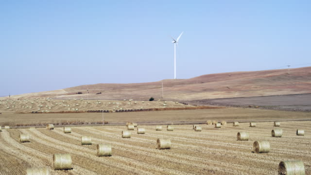 Wind Turbines and hay bales.