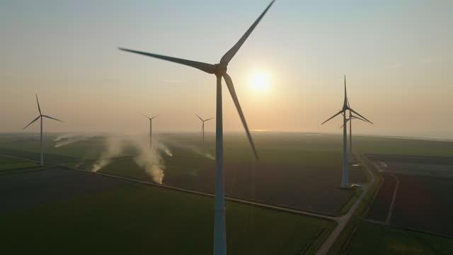 wind turbines and smoke in fields at sunset - hållbar energi bildbanksvideor och videomaterial från bakom kulisserna