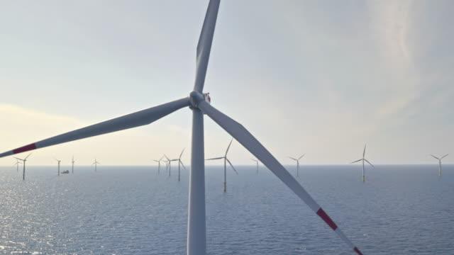 aerial wind turbines at sea rotating in sunshine - wind turbine stock videos & royalty-free footage