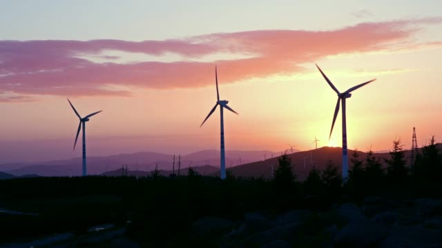 vídeos de stock e filmes b-roll de 4k: wind turbines at sunrise in dramatic sky - três objetos