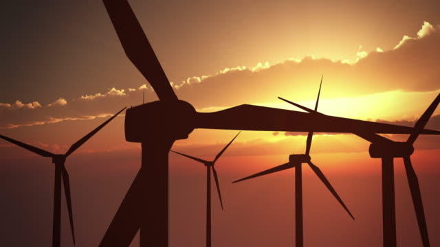 wind turbines at sunset | loopable - windmill stock videos & royalty-free footage