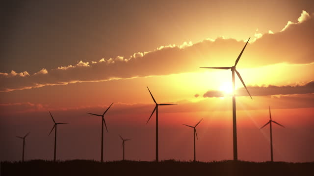 wind turbines at sunset | loopable - wind turbine stock videos & royalty-free footage