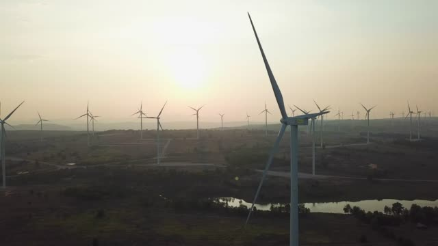 wind turbines at sunset producing renewable energy - land stock videos & royalty-free footage
