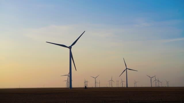 vídeos de stock, filmes e b-roll de turbinas eólicas ao pôr do sol produzindo energia renovável - electrical equipment