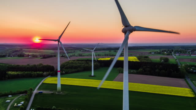 AERIAL: Wind turbines at sunset - renewable energy