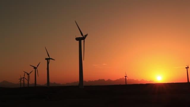 wind turbines at sunset sky background - sinai egitto video stock e b–roll