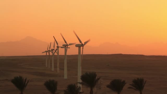 wind turbines at sunset sky background - renewable energy stock videos & royalty-free footage