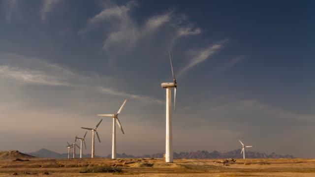 Wind turbines at sunset sky background