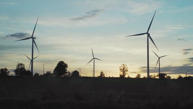 windkraftanlagen in landwirtschaftlichen feldern bei sonnenuntergang. - landwirtschaftsminister stock-videos und b-roll-filmmaterial