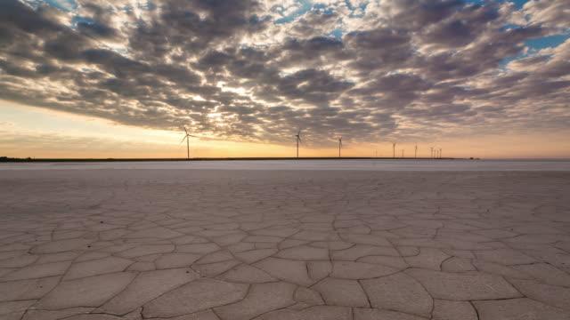 vídeos y material grabado en eventos de stock de wind turbines in desert with cracked earth at sunrise. green energy concept. timelapse - huella de carbono