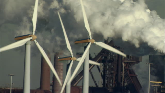 CU Wind turbines in front of power plant emitting cloud of steam / Merseyside, North Sea, United Kingdom