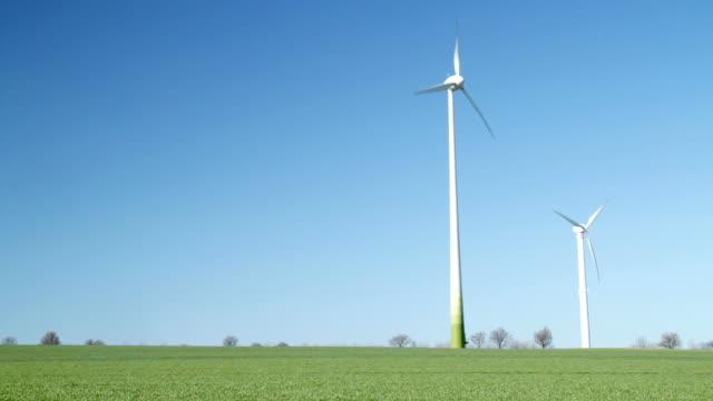 vídeos de stock e filmes b-roll de turbinas eólicas no campo verde - turbina