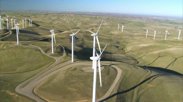 LOW AERIAL Wind turbines in green hills / San Francisco, California, USA