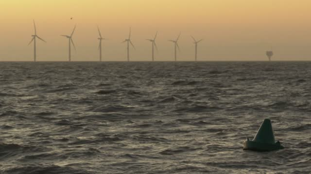 wind turbines off the coast on november 18, 2020 in clacton-on-sea, england. wind energy features prominently in prime minister boris johnson's plan... - renewable energy stock videos & royalty-free footage
