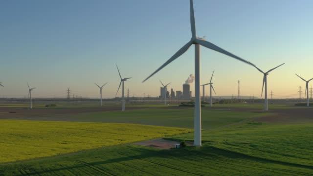 wind turbines on a field (sunset) - sustainable energy点の映像素材/bロール