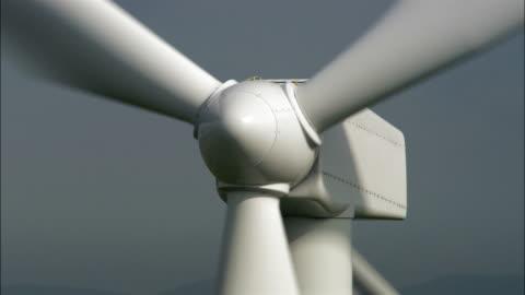 low aerial, cu, zo, wind turbines on field, ceredigion, wales - 風力発電点の映像素材/bロール