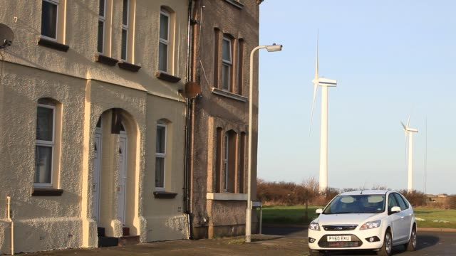 wind turbines on the west coast of cumbria near workington close to terraced housing. - green colour stock videos & royalty-free footage