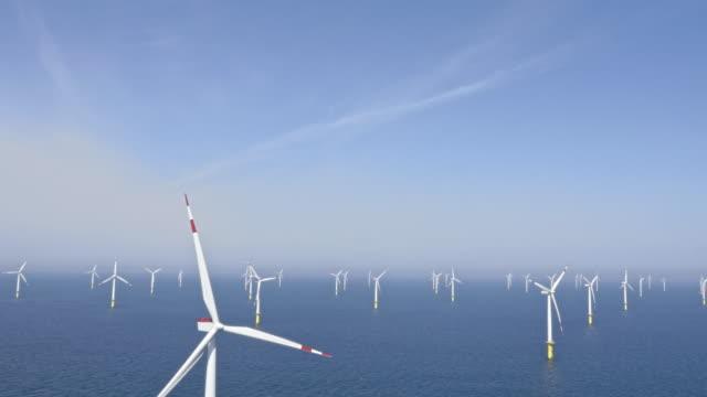 aerial wind turbines producing renewable energy at sea - tilt down stock videos & royalty-free footage