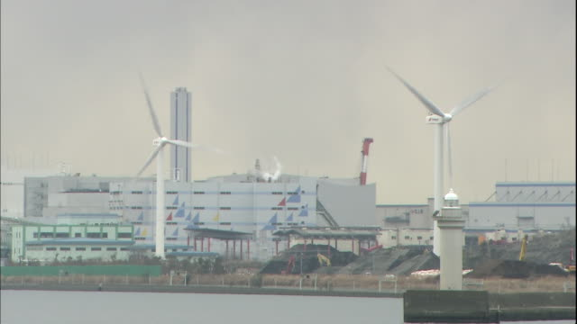 wind turbines rotate as they generate electricity near the tokyo gate bridge. - ariake sea stock videos and b-roll footage