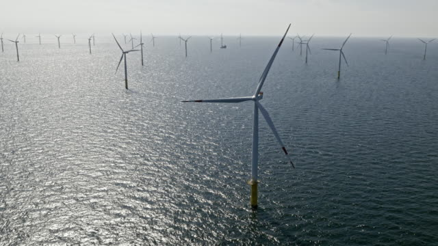 aerial wind turbines rotating in sun at sea - propeller stock videos & royalty-free footage