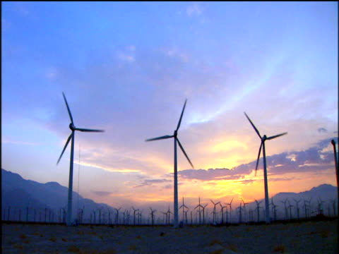 wind turbines rotating silhouetted against orange sunset and blue sky - energia rinnovabile video stock e b–roll