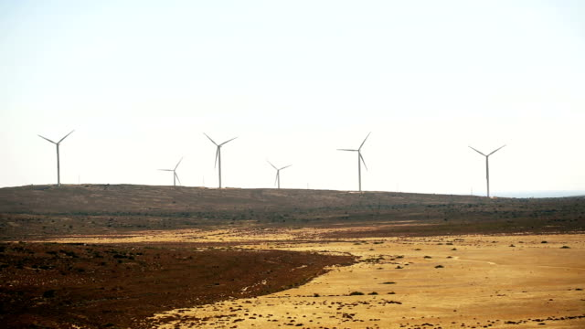 Wind turbines seen in the open field with horizont over the land