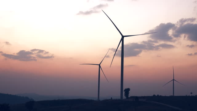 wind turbines silhouetted against a clouds sky - windmill stock videos and b-roll footage